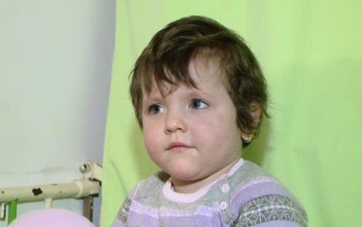 Fetița hrănită cu ceai și pufuleți