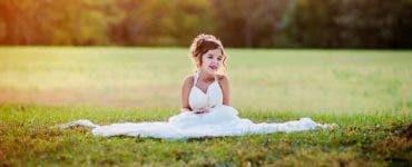 O fetiță a îmbrăcat rochia de mireasă a mamei sale.
